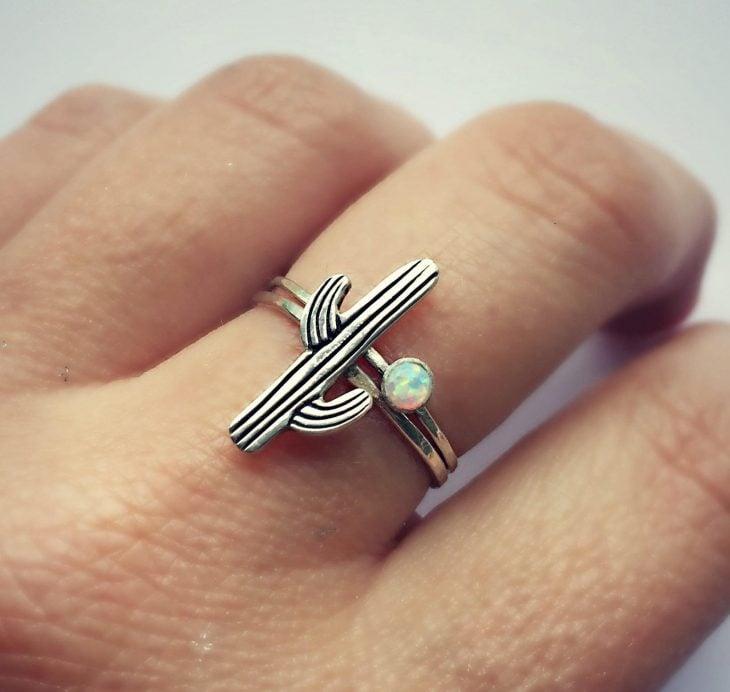 Mano de mujer con anillo en forma de cactus