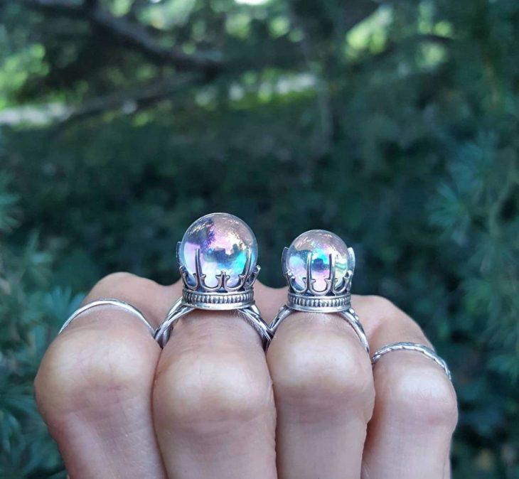 Mano de mujer con anillos en forma de bola de cristal