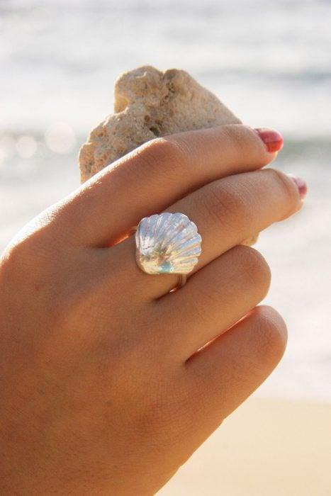 Mano de mujer con anillo de concha