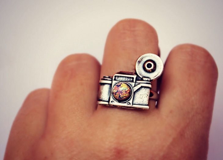 Mano de mujer con anillo en forma de cámara antigua