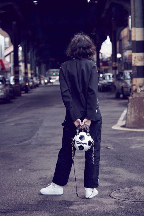 Chica sosteniendo un bolso hecho con pelota de futbol