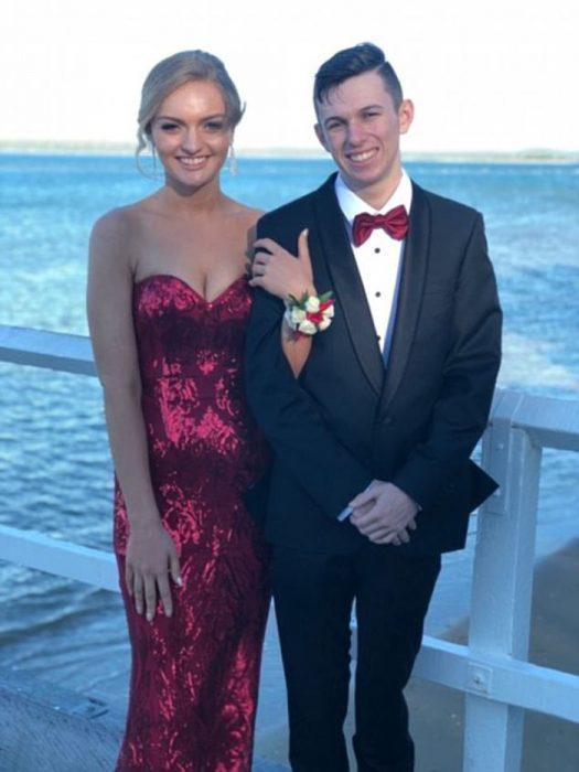 Chica sujetando del brazo a un chico que fue su cita en el baile de graduación
