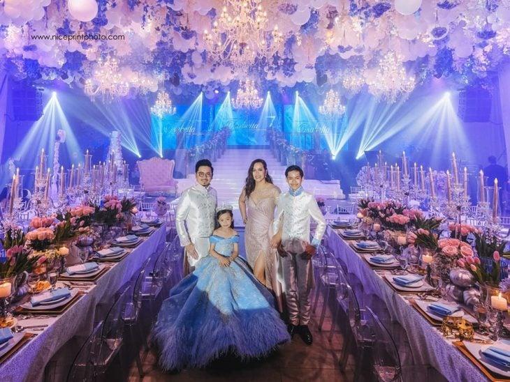 niña con vestido azul y corona en fiesta y familia