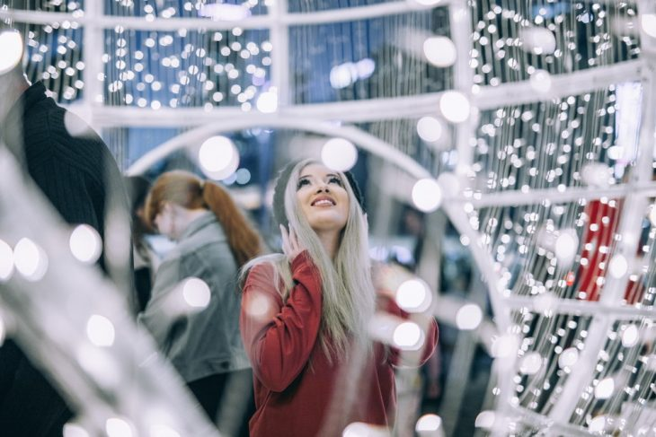 chica bajo luces navideñas