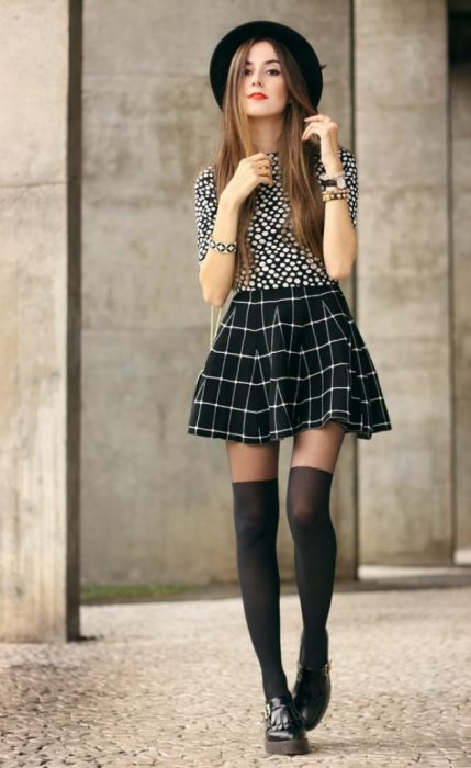 Chica con onda juvenil usando falda skater a cuadros y zapatos masculinos
