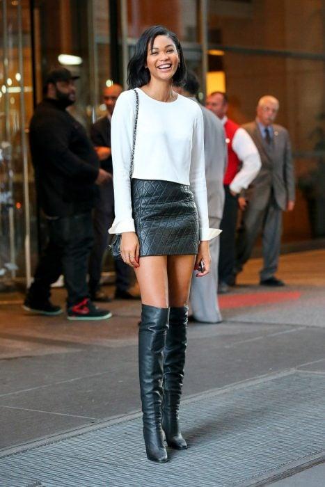 Chica sonriendo con falda negra de piel y botas negras largas