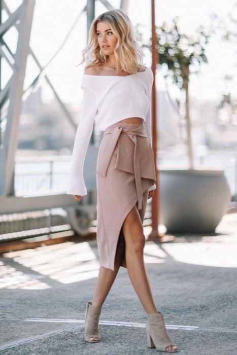 Chica rubia posando con una falda beige envolvente y tacones de columna
