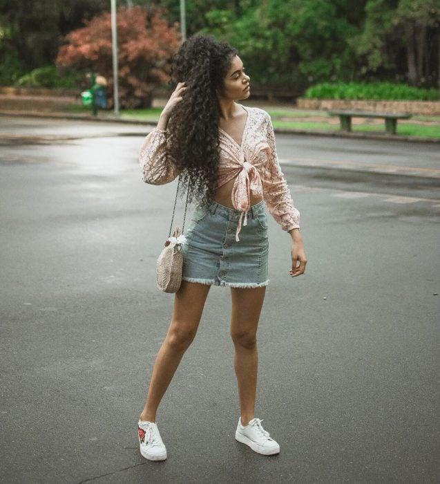 Chica de cabello chino en medio de la calle con una falda de mezclilla y tenis