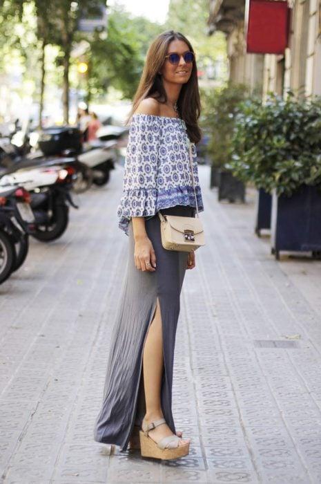 Chica en la calle vistiendo una maxifalda gris con sandalias estilo cuña