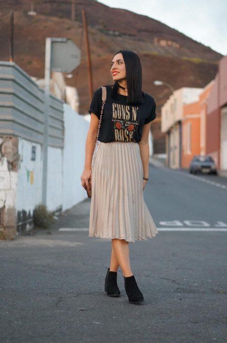 Chica en la calle con playera de Guns and roses, falda plisaba beige y botines negros