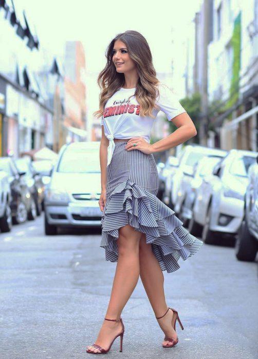 Chica caminando por la calle con una playera blanca, falda corte sirena y sandalias de taacón