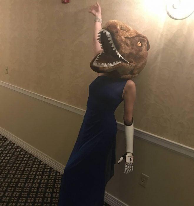 Dama de honor usando una mascara de dinosaurio
