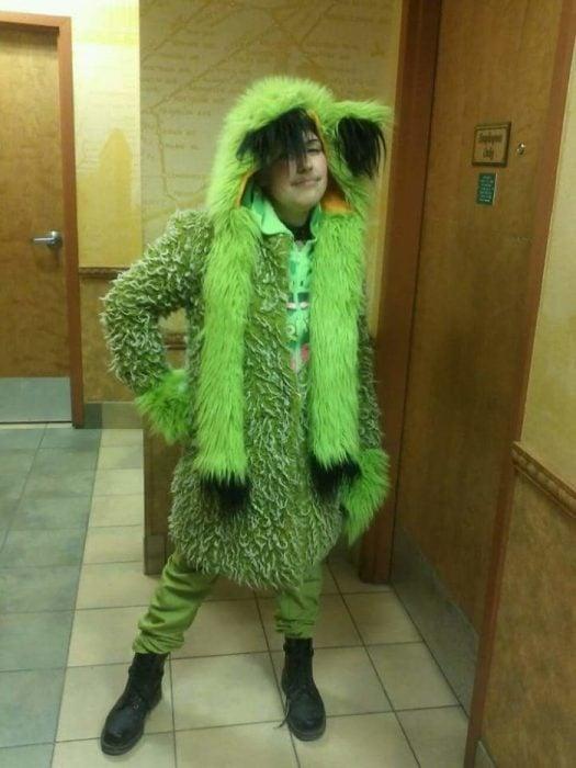 Chico usando un traje de peluche de color verde