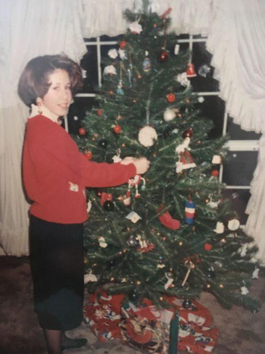 Niña que parece señora colocando el árbol de navidad en los 90