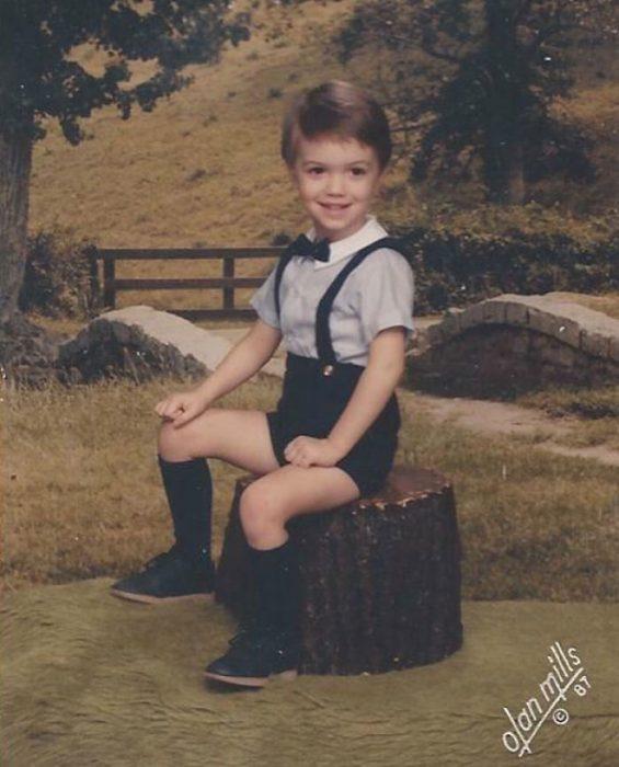 Chico sentado en un tronco usando un traje de short