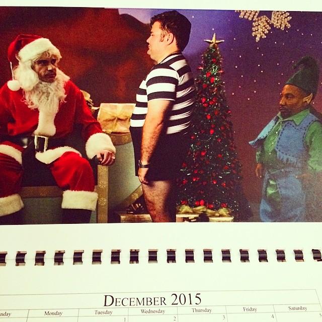 Hombre posando en un calendario como un niño junto a santa y un duende