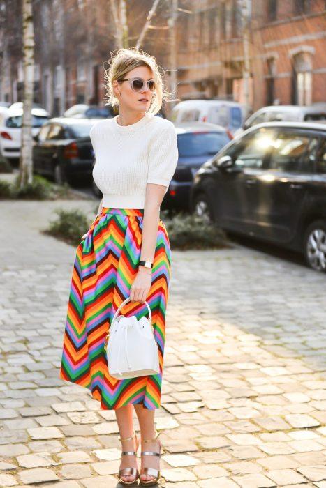 mujer con camisa blanca y falda de arcoiris