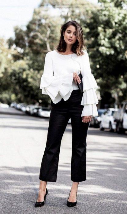 mujer con blusa blanca de olanes en las mangas