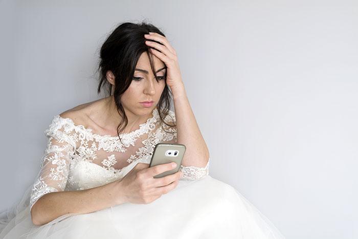 Novia sosteniendo un celular mientras lee los mensajes de infidelidad de su novio
