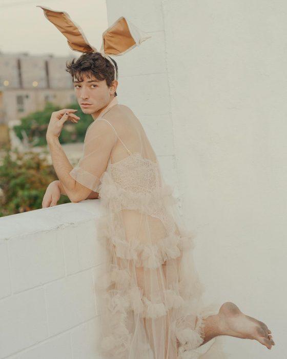 Chico descalzo vestido con oreas de conejo y bata de dormir
