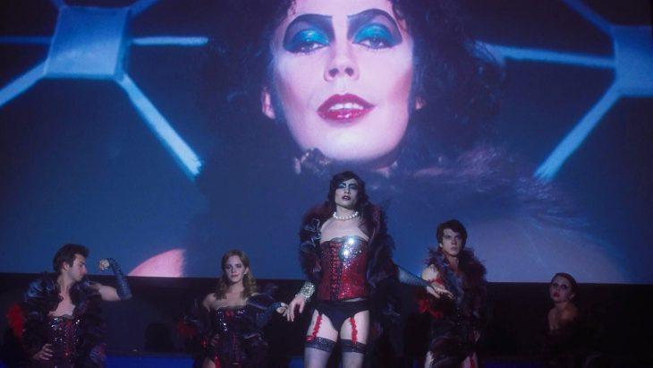 Chico maquillado vistiendo un corsette rojo y medias
