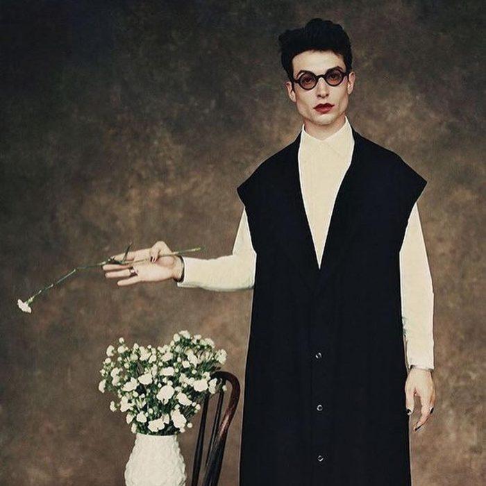 Chico usando lentes redondos y vistiendo un conjunto largo negro y blanco