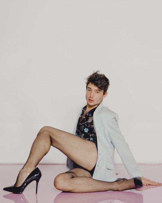 Chico posando en el suelo con saco de vestir y tacones