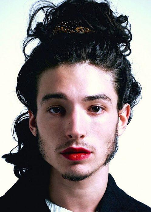 Chico de cabello largo usando un chongo y labial rojo