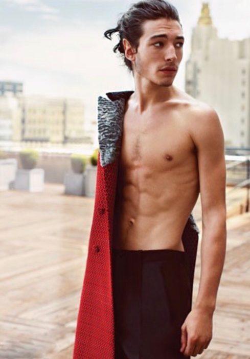Chico con abdomen marcado y cabello largo cargando una gabardina roja en el hombro