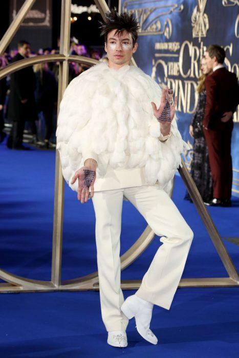 Chico vestido de blanco con abrigo de plumas y manos borroneadas