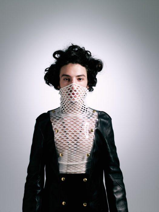 Chico vistiendo una blusa de red blanca y un saco con plástico en el pecho