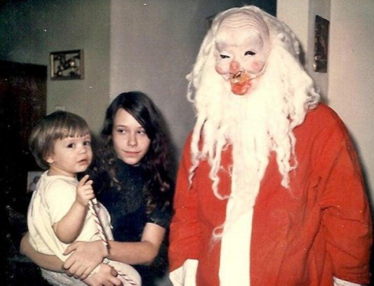 Santa Claus que da miedo al lado de dos niños