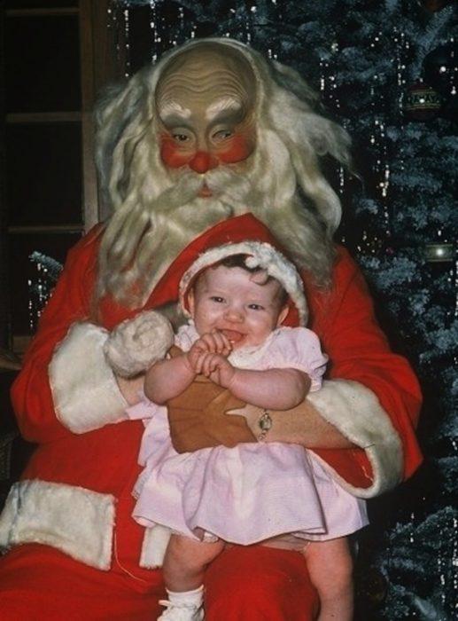 Santa Claus que da miedo cargando a una niña