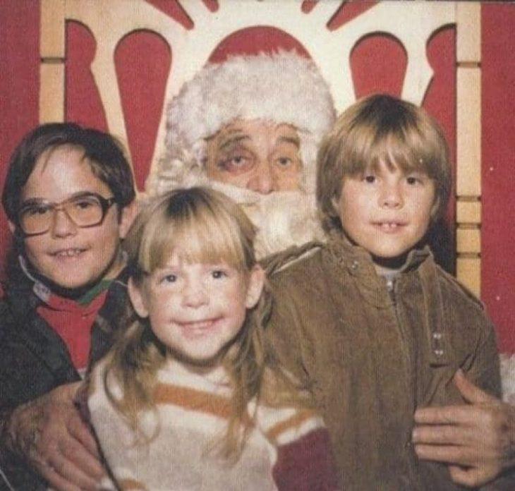 Santa Claus que da miedo cargando a tres niños