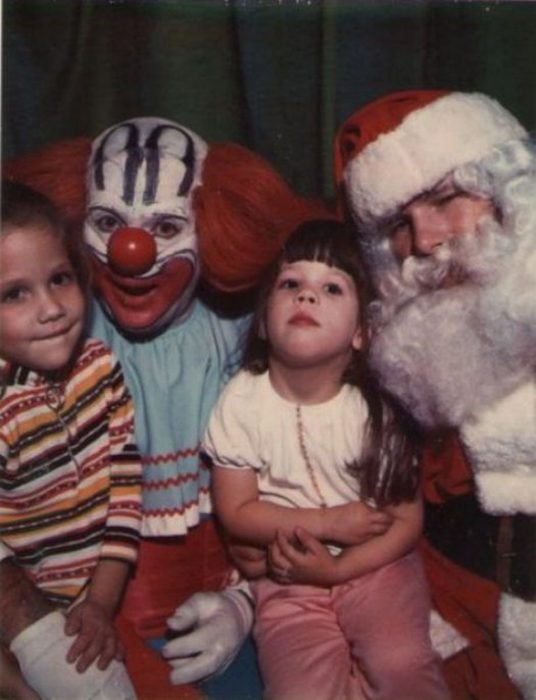 Santa Claus que da miedo junto a un payaso cargando a dos niños