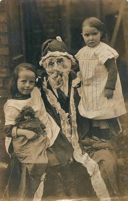Santa Claus que da miedo cargando a dos niños