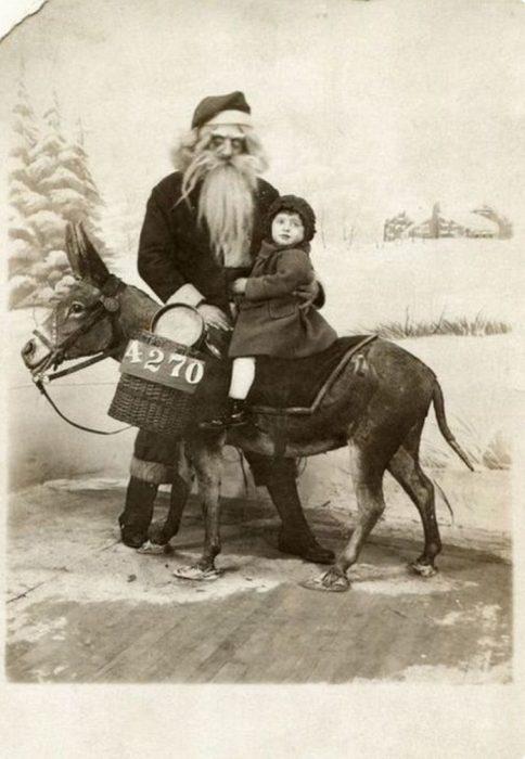 Santa Claus que da miedo al lado de un burro que lleva a una niña
