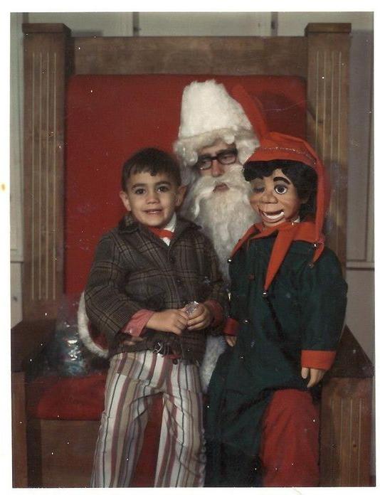 Santa Claus que da miedo cargando a un niño y a un muñeco ventrílocuo