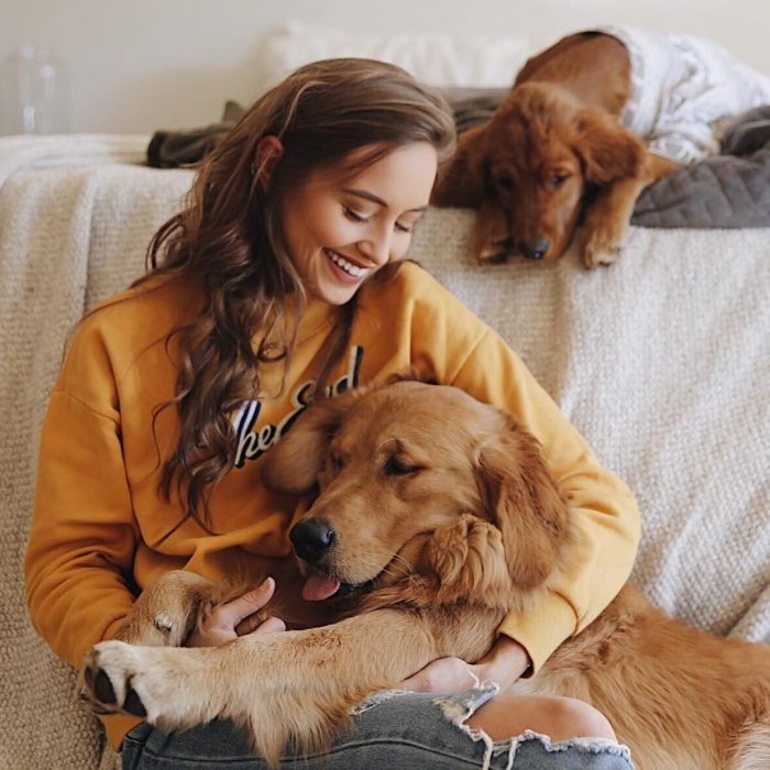 Chica con hoddie anaranjado sentada con sus dos perros golden retriever