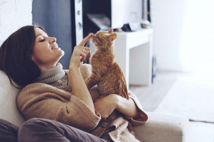 Chica de cabello corto y suéter café sonriendo y sostendiendo a un gato anaranjadi