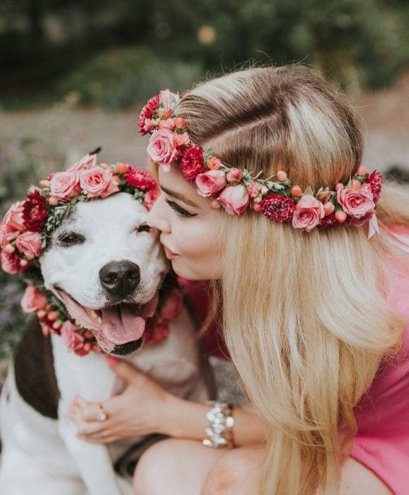 Chica rubia con corona de flores abrazando a un perro sonriente con corona de flores