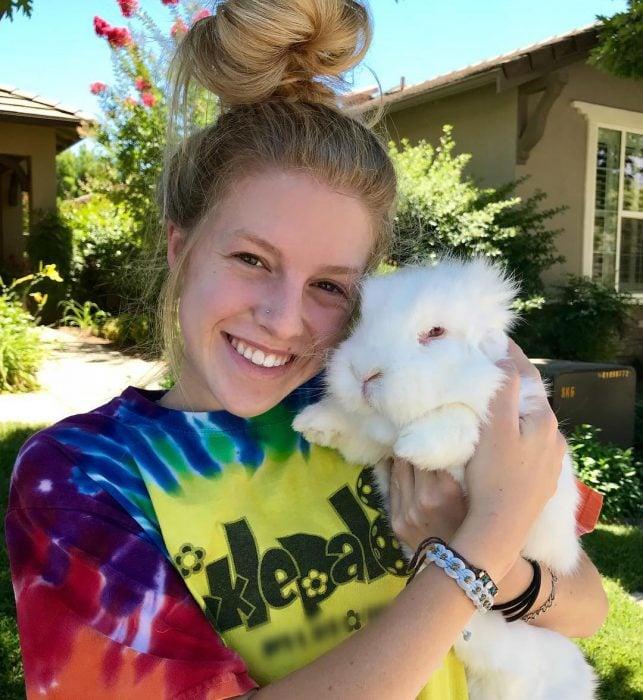 Chica de cabello rubio con un chongo y playera de colores abrazando a un conejo blanco
