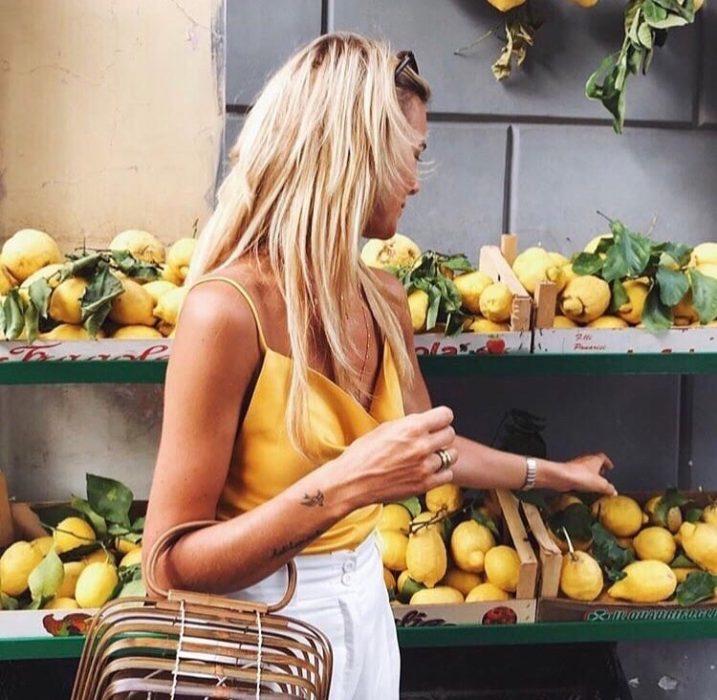 chica comprando limones en el supermercado