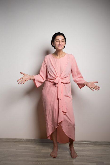 Mujer usando un vestido de color rosa con un moño delantero