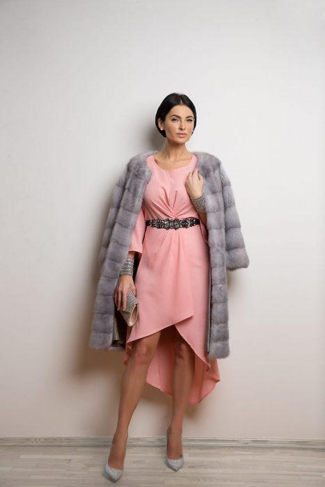 Mujer usando un vestido de color rosa y un abrigo de peluche en color gris