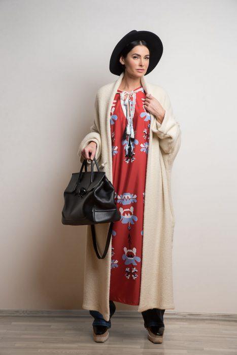 Mujer usando un vestido boho, pantalón de mezclilla y abrigo largo