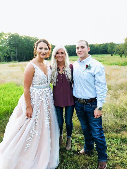 Chica que donó su boda a una pareja que la necesitaba posando junto a los novios