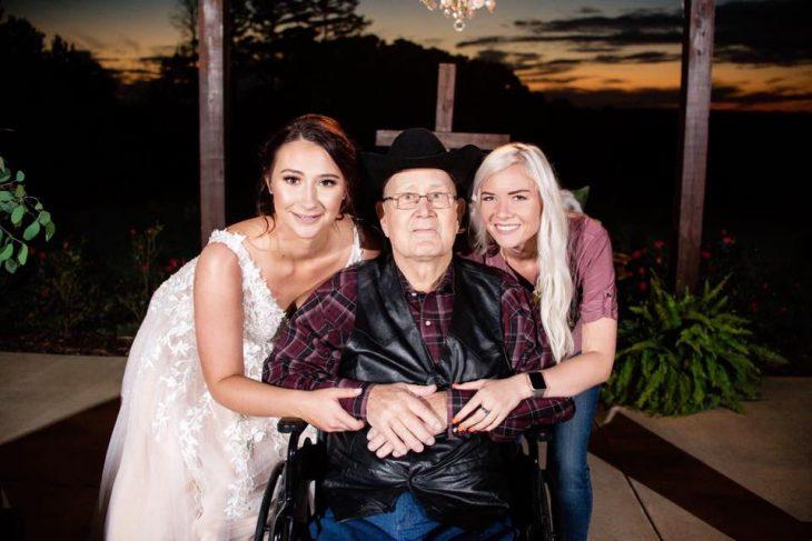Novia posando junto a su abuelo y la chica que le regaló una boda