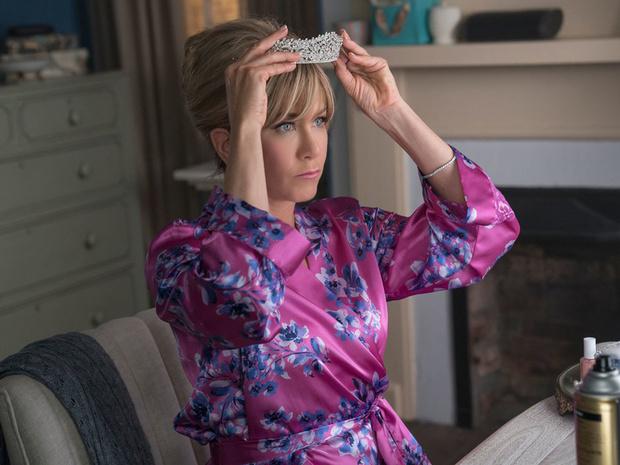 Jennifer Aniston poniendose una tiara en la cabeza en su nueva película de Netflix