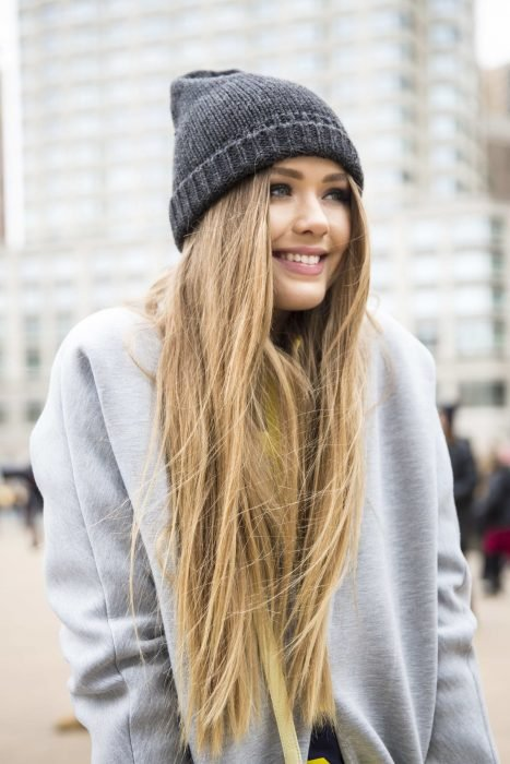Chica de cabello rubio y largo con gorra de invierno y sudadera